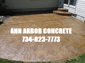 Picture of stamped concrete patio with Ann Arbor Concrete name and phone number.